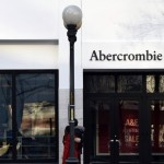 An Abercrombie & Fitch storefront and sign in downtown Seattle, Washington. Pedestrians and lamp posts are on the sidewalk outside the store.